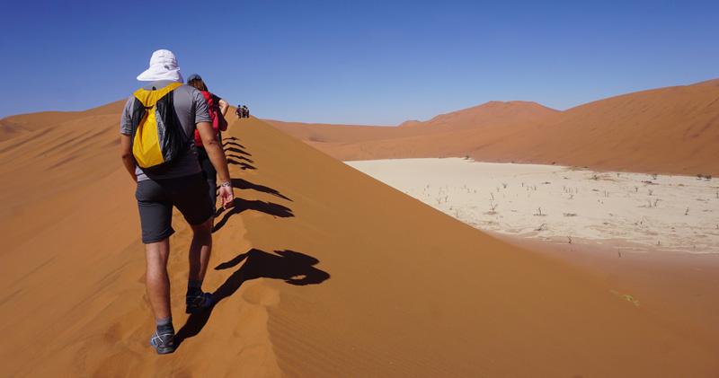 gruppo di persone che cammina su una duna del deserto