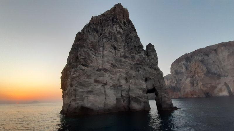 Faraglione in mezzo al mare con tramondo