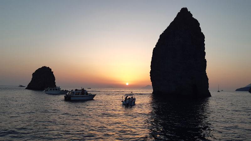 Scogli in mezzo al mare con barche al tramonto