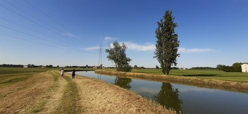 persone che passeggiano vicino ad un fiume